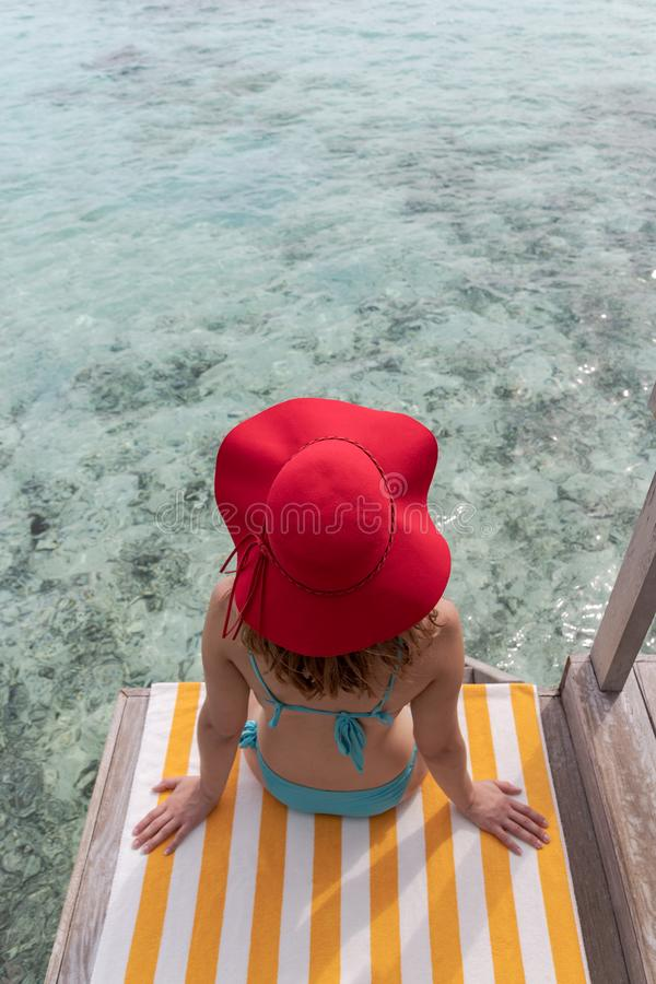 Young woman with blue bikini and red hat on a towel over crystal clear blue water royalty free stock photography