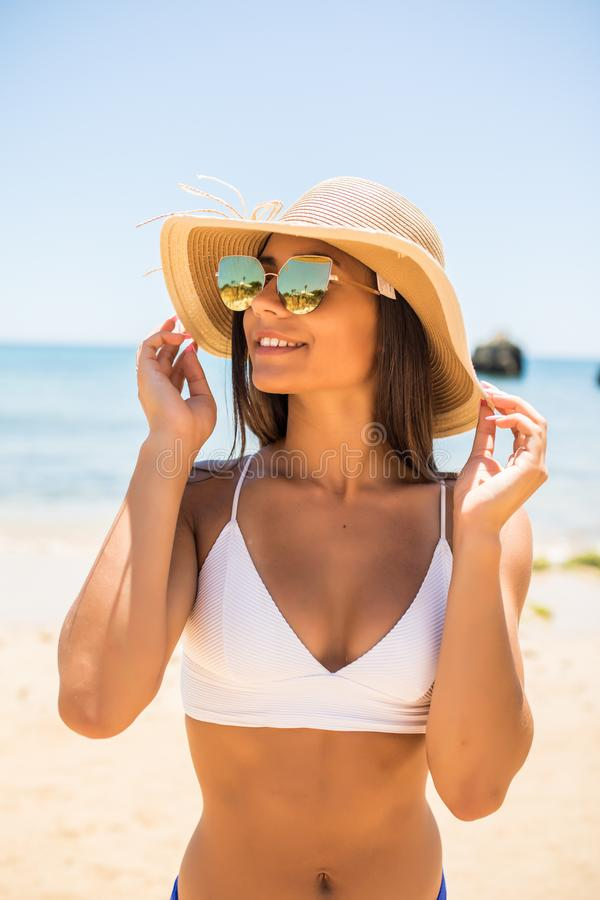 Young woman in blue bikini wearing white straw hat enjoying summer vacation at beach. Portrait of beautiful latin woman relaxing a stock image