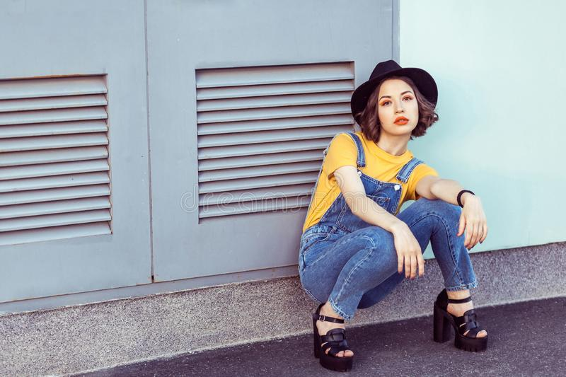 Young woman in blue denim overalls and yellow tshirt with black hat sensual looking at camera while posing near industrial royalty free stock image