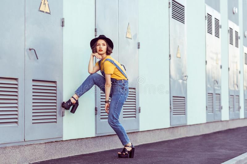 Young woman in blue denim overalls and yellow tshirt with black hat sensual looking at camera while posing near industrial stock photography