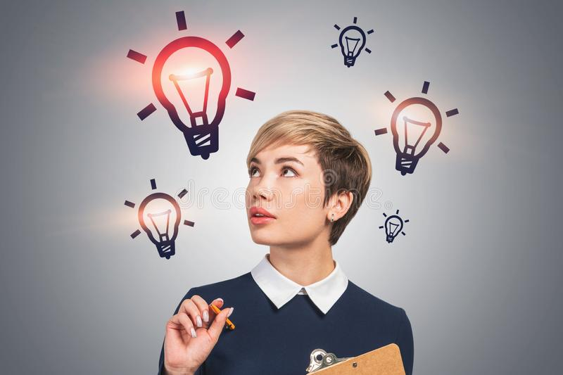 Woman with clipboard and lightbulbs royalty free stock image
