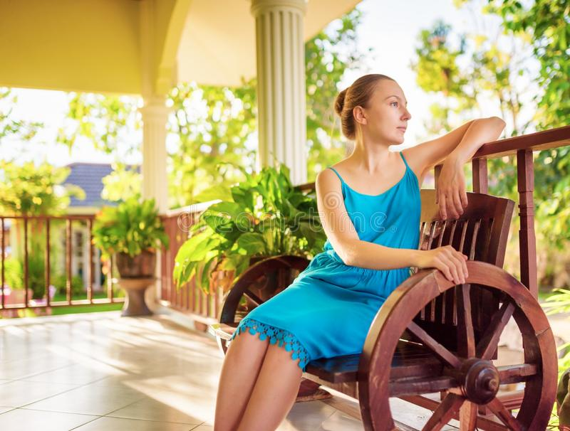 Young woman in blue dress relaxing in house terrace stock image