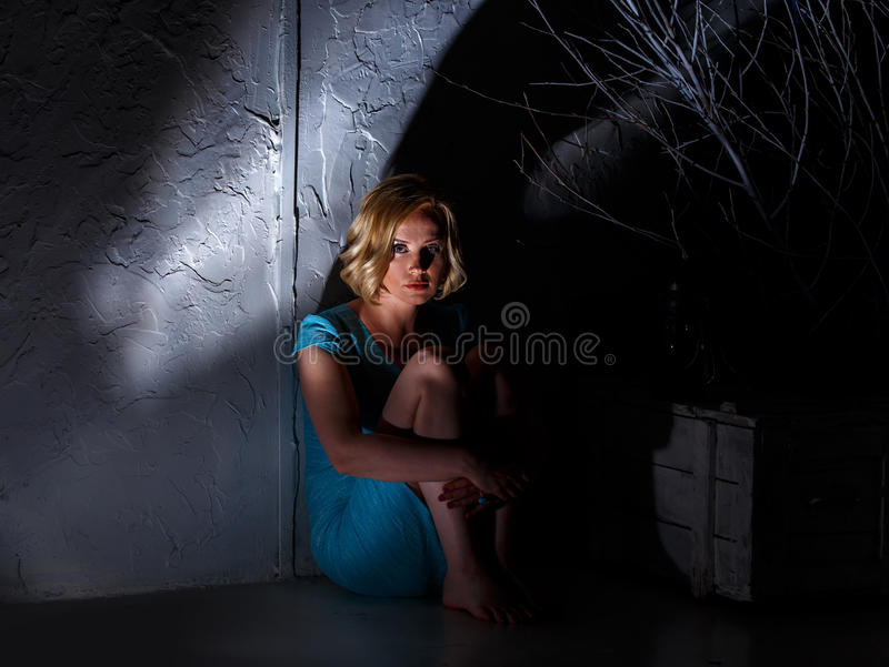 Young woman in blue dress sitting in dark horrible place royalty free stock image