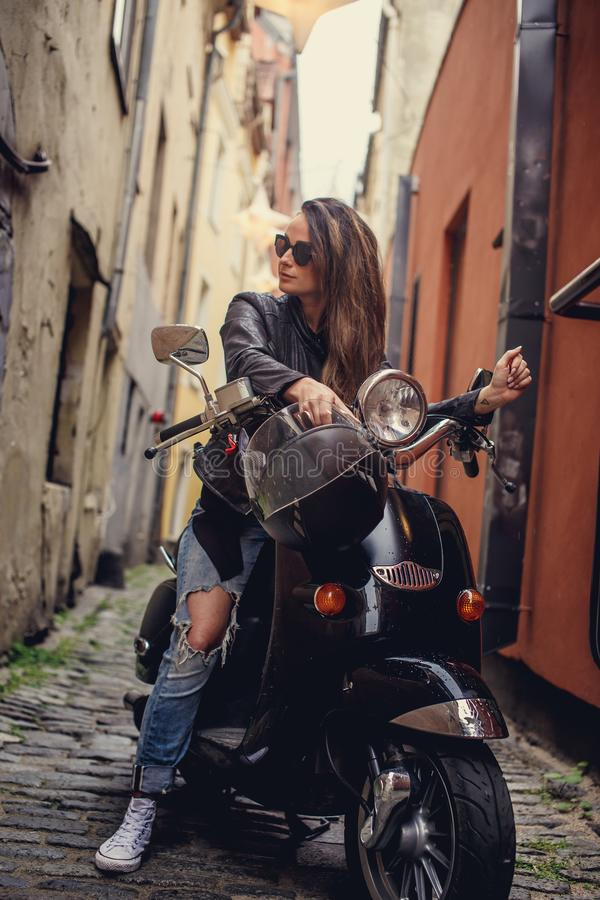 Young woman in blue jeans and leather jacket stock photo