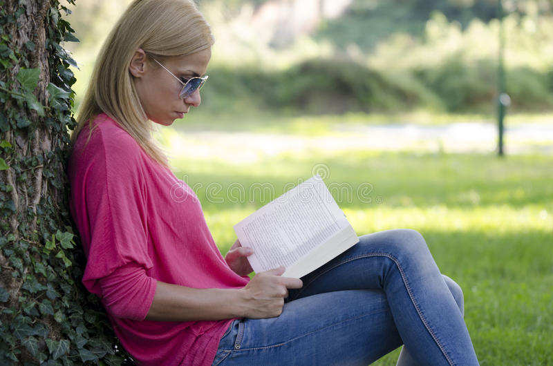 Young woman in blue jeans reading book. royalty free stock photos