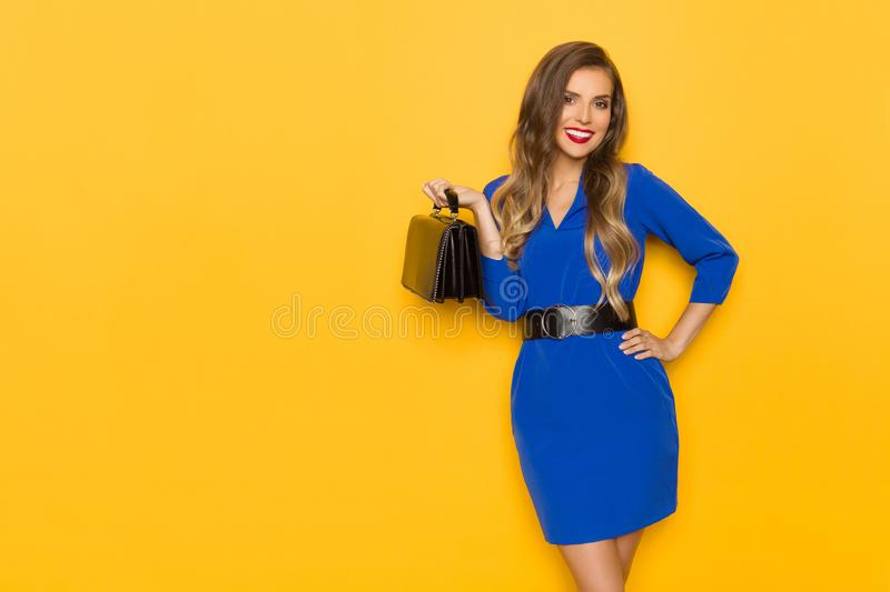Young Woman In Blue Mini Dress Is Posing With Black Leather Bag stock photo
