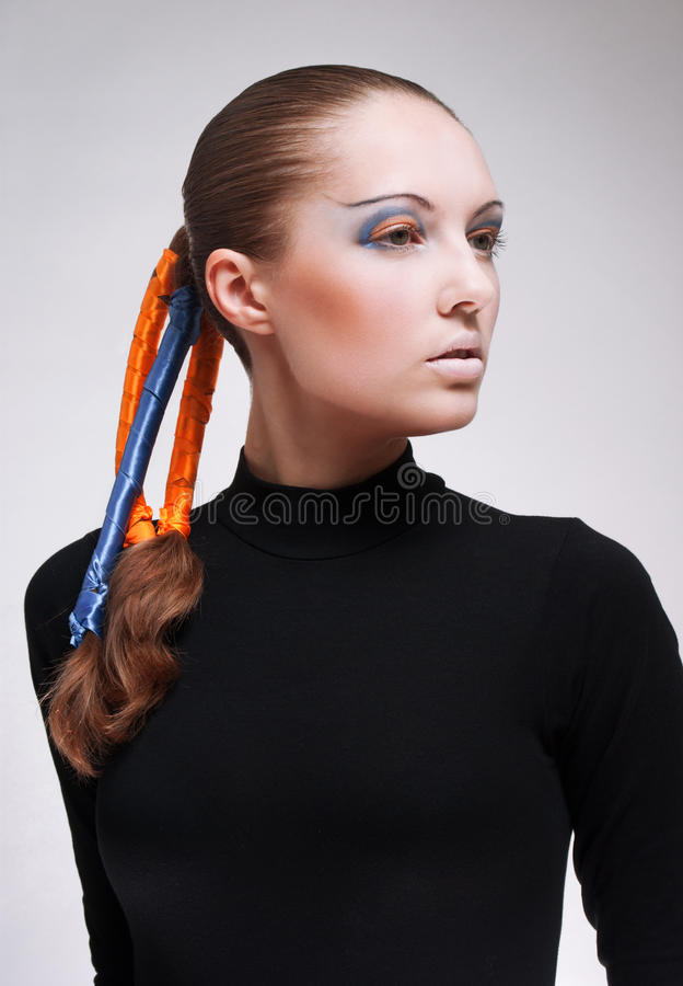 Young woman with blue and orange ribbons in hair stock images