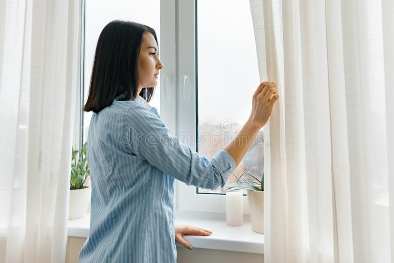 Young woman in blue shirt opening curtains looking out the window in the morning in the room, cloudy day in the city stock photography