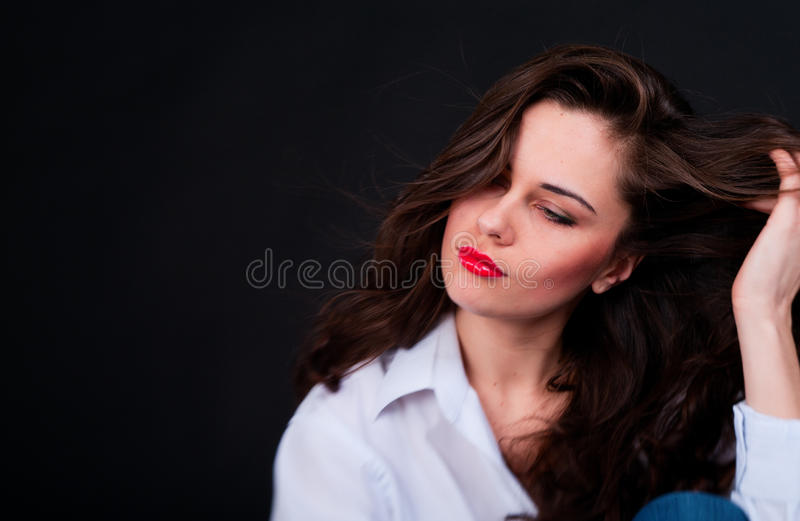 Young woman in blue shirt with weaving long hair and semiclosed royalty free stock photos
