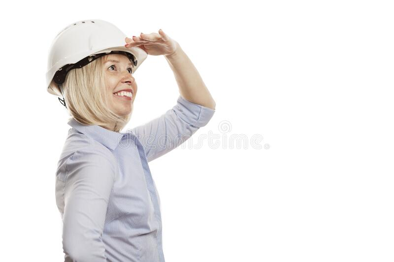 A young woman in a blue shirt and white construction helmet looks into the distance. Isolated over white background. Close-up. stock photo