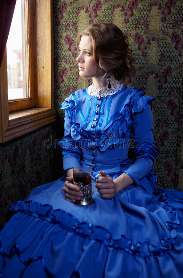 Young woman in blue vintage dress sitting in coupe of retro rai stock photography