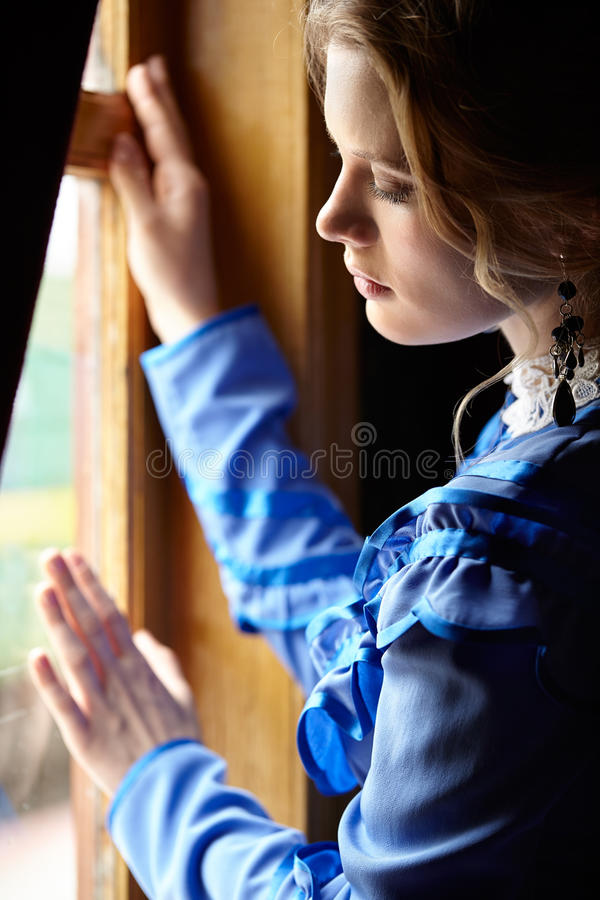 Young woman in blue vintage dress standing near window in coupe stock photography