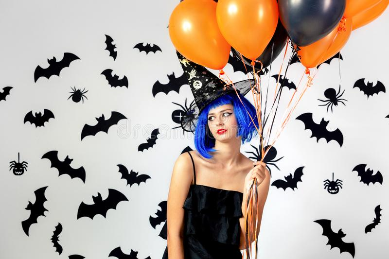 Young woman in a blue wig and witch`s hat black and orange balloons on a white background with black bats and spiders stock photo