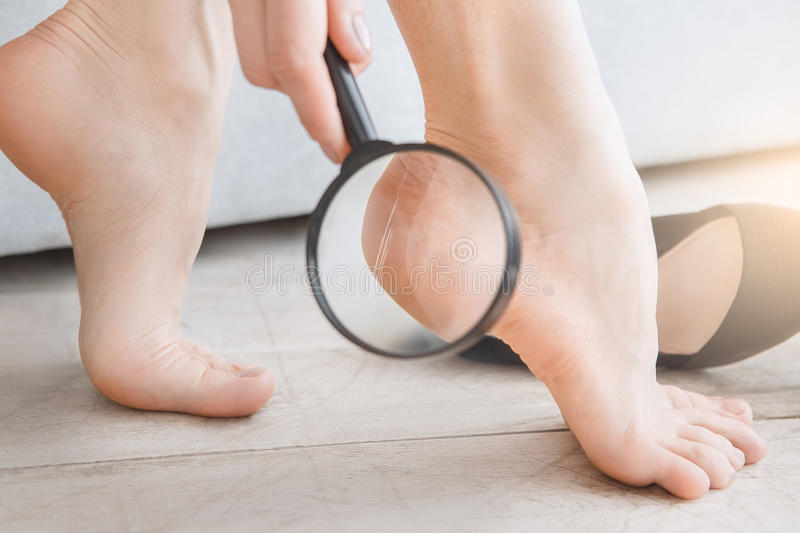 Young woman body care at home indoors. Young female body care at home rub feet stock photography
