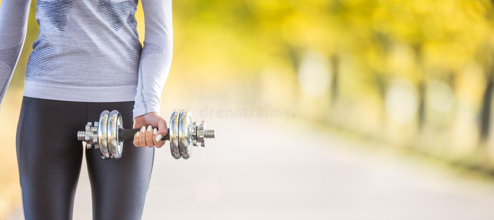 Young woman body in fitness wear exercising with dumbbell and headphones stock photography