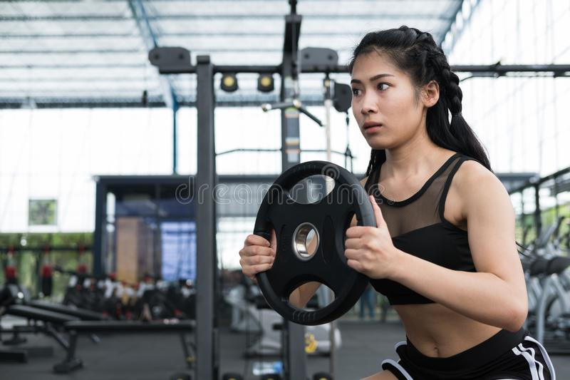 young woman bodybuilder execute exercise in fitness center. female athlete lift heavy weight barbell plate in gym. sporty girl royalty free stock images
