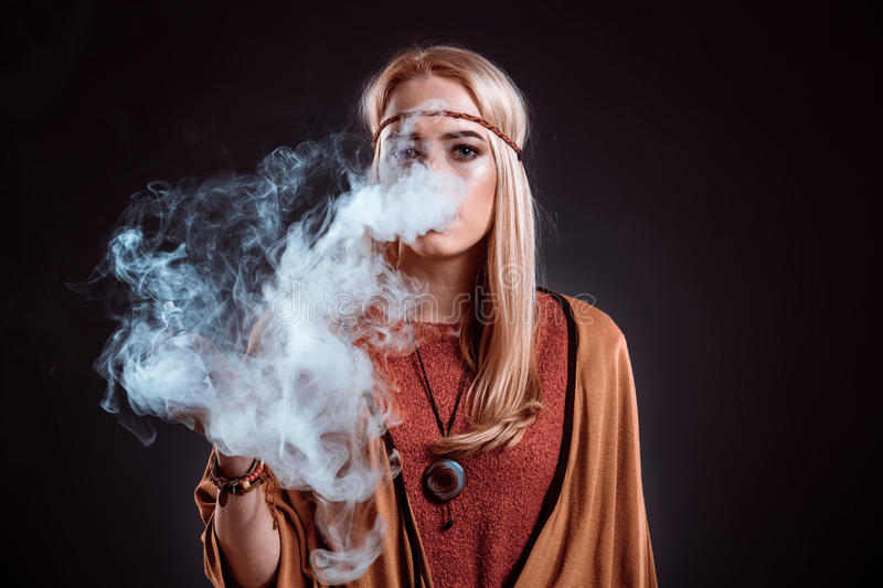 Young woman in the Boho style blowing smoke. The blonde on a dark background. Young woman looking into the camera royalty free stock photos
