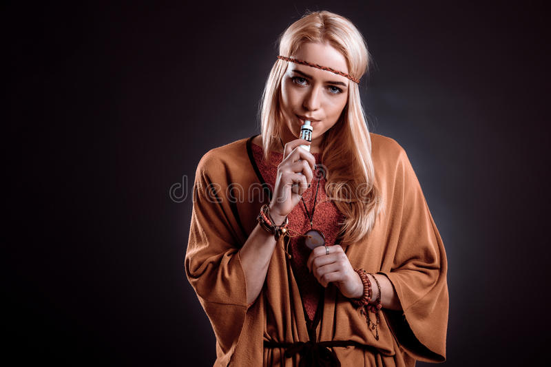 Young woman in the Boho style blowing smoke. The blonde on a dark background. Young woman looking into the camera royalty free stock photography