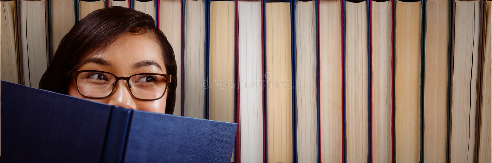 Young woman with a book looking right in front of books royalty free stock images