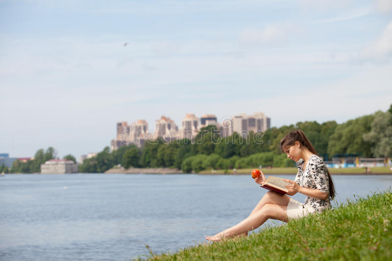 Young woman with the book in the park. royalty free stock images