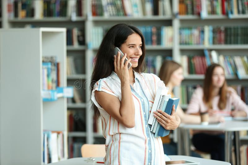 Young woman with books talking on phone royalty free stock photography