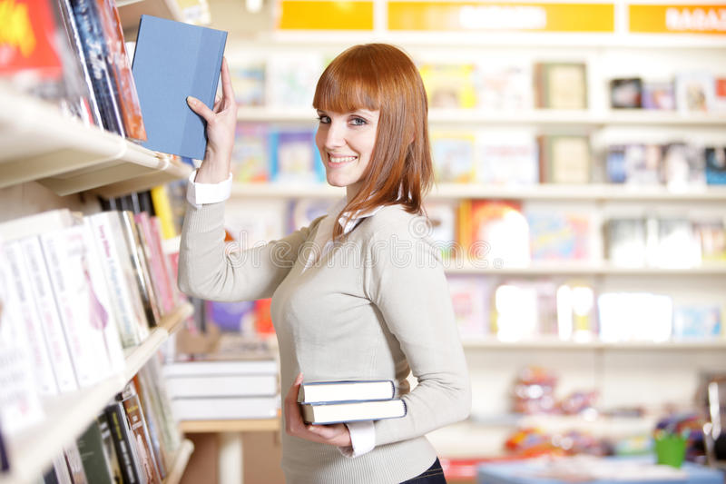 Young woman in a bookstore. Young woman looking for a book in a bookstore stock image