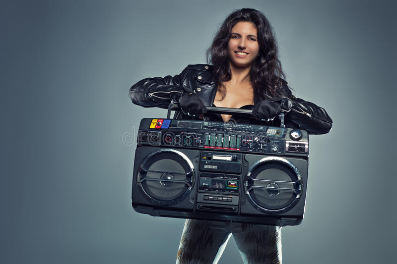 Young woman with boom box. Young smiling brunette woman in black leather jacket holding big old boom box royalty free stock photography