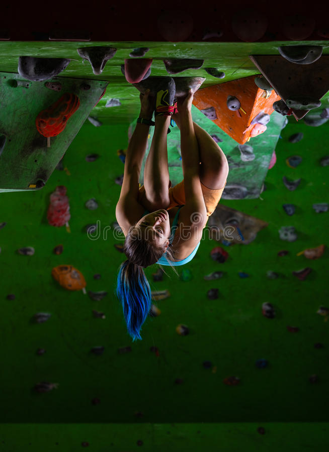 Young woman bouldering on ceiling of climbing gym. Young woman bouldering on ceiling of indoor climbing gym royalty free stock images