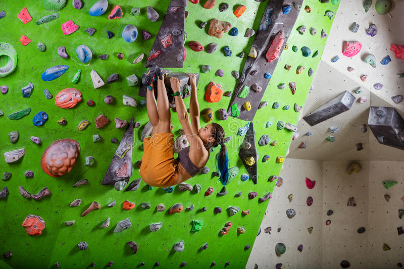Young woman bouldering in climbing gym. Young strong woman bouldering in climbing gym stock images
