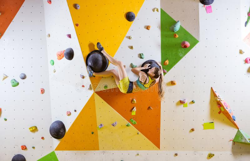 Young woman bouldering in indoor climbing gym. Young woman bouldering challenging route in indoor climbing gym stock images