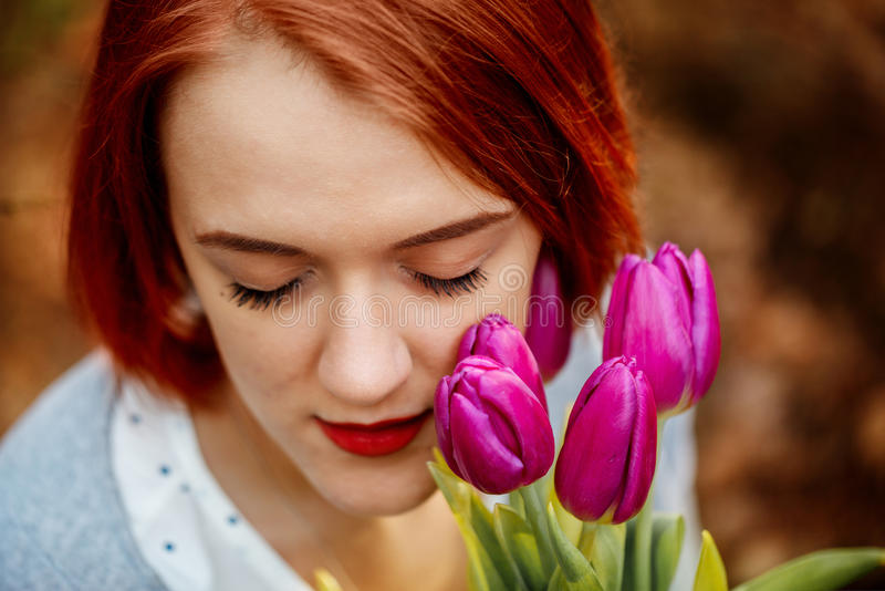 Young woman with a bouquet of tulips at the park in early spring royalty free stock photo