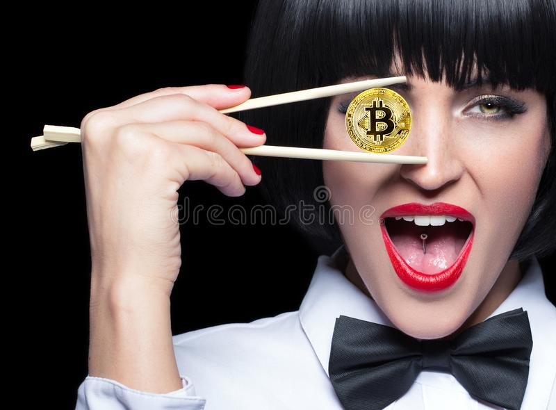 Young woman in bow tie holding bitcoin in front of eye. Young woman in bow tie and wig holding gold bitcoin coin by chopsticks in front of eye, isolated on black stock photos