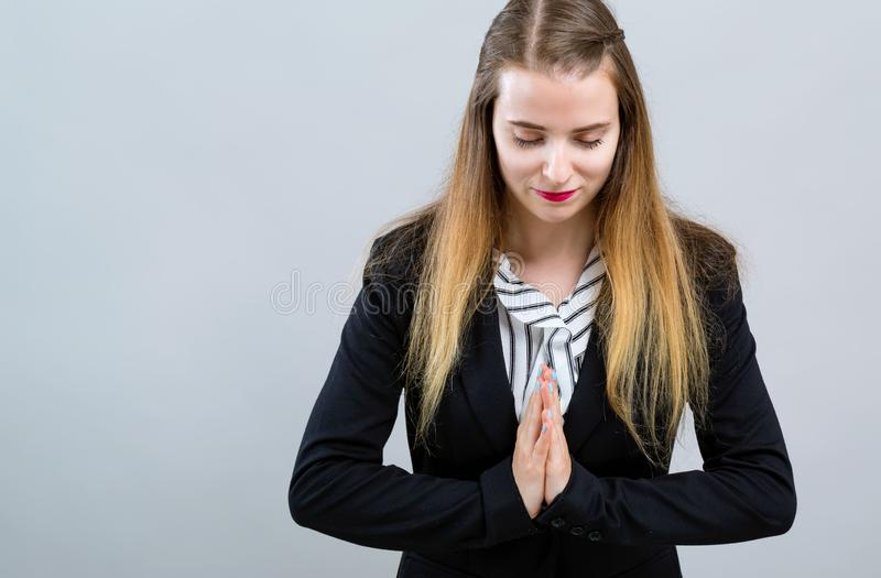 Young woman bowing. With hands together on a gray background royalty free stock image