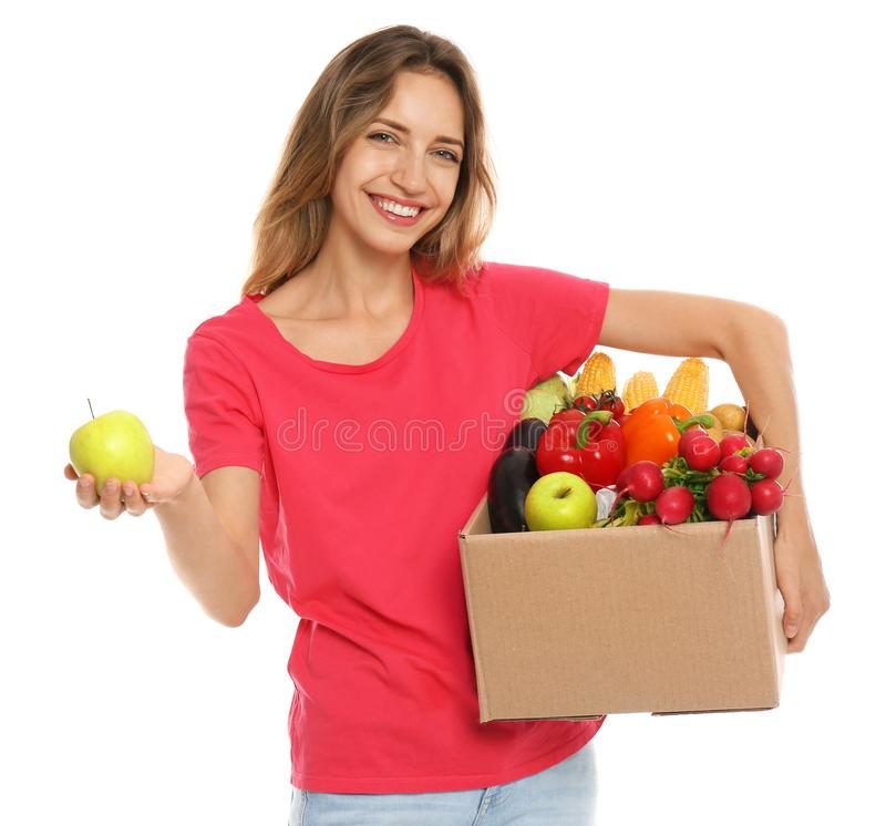 Young woman with box of fresh vegetables on white stock image
