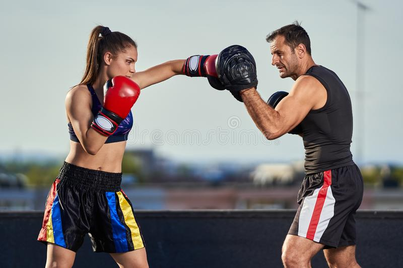 Young woman boxer hitting pads outdoor. Young boxer girl with her coach hitting mitts outdoor on a roof in urban environment royalty free stock photo