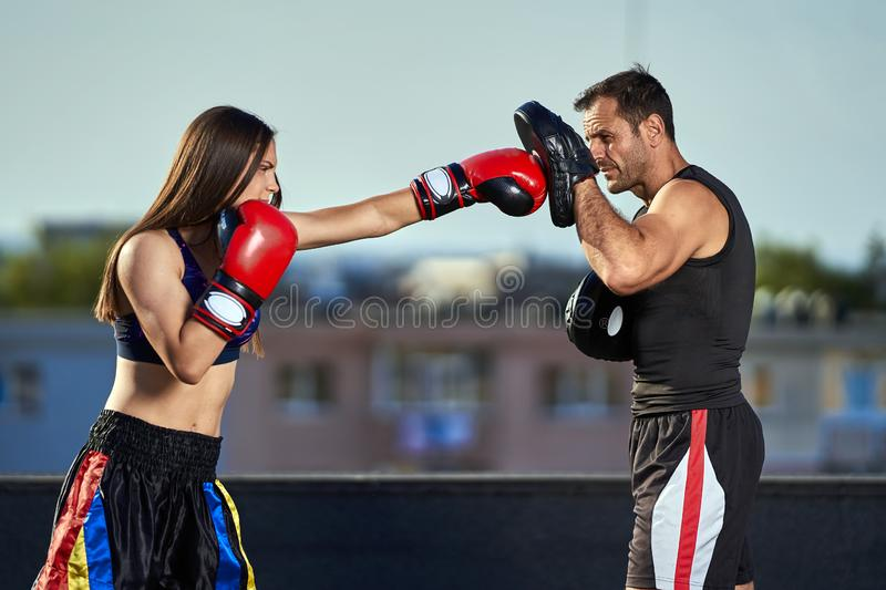 Young woman boxer hitting pads outdoor. Young boxer girl with her coach hitting mitts outdoor on a roof in urban environment royalty free stock images