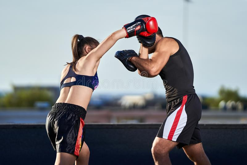 Young woman boxer hitting pads outdoor. Young boxer girl with her coach hitting mitts outdoor on a roof in urban environment stock photo