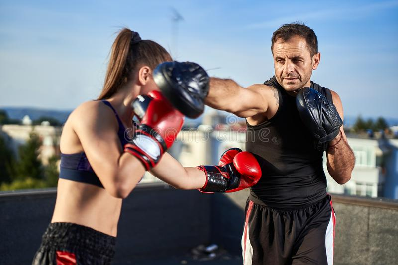Young woman boxer hitting pads outdoor royalty free stock photography