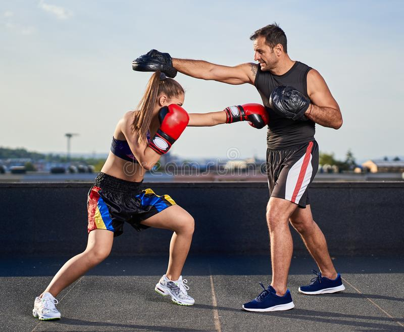 Young woman boxer hitting pads outdoor royalty free stock photos