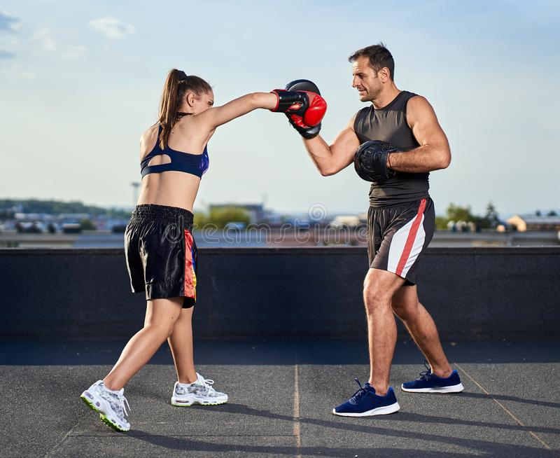 Young woman boxer hitting pads outdoor stock image