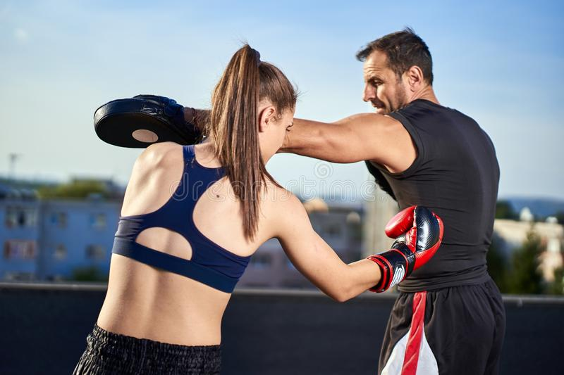 Young woman boxer hitting pads outdoor stock images