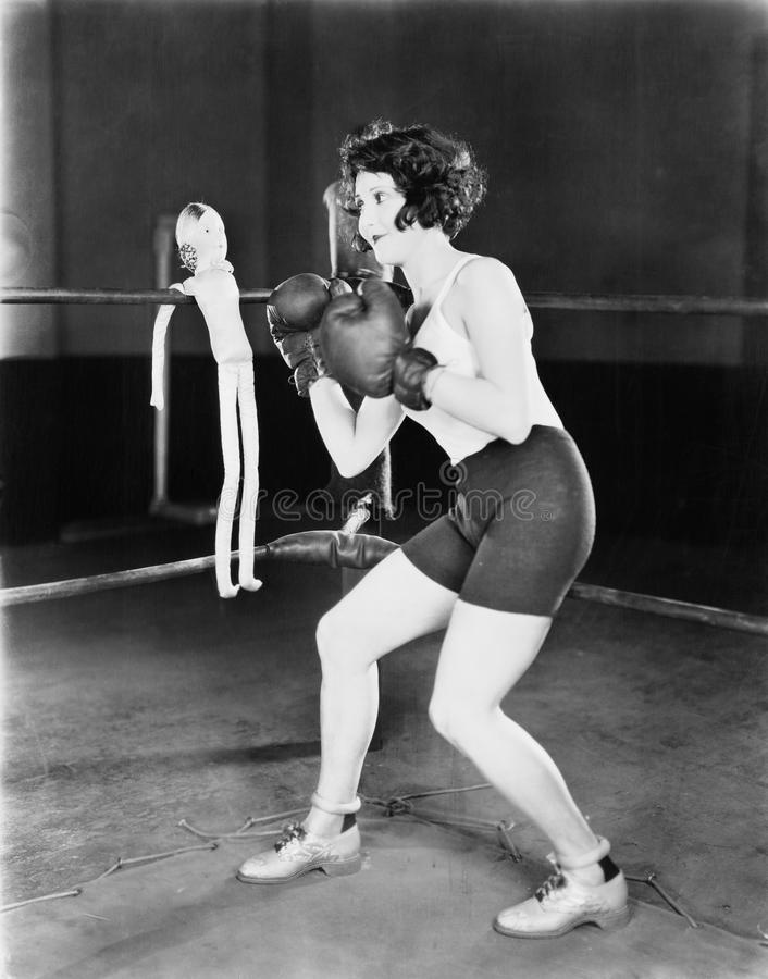 Young woman with boxing gloves with a doll on the ropes stock image