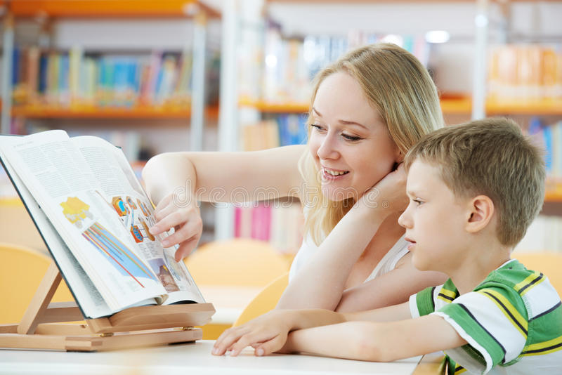 Young woman and boy reading book in library stock photos