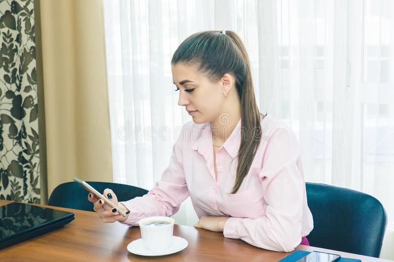 A young woman during a break in the workplace watching the news through a smartphone. Coffee break in the office royalty free stock photo