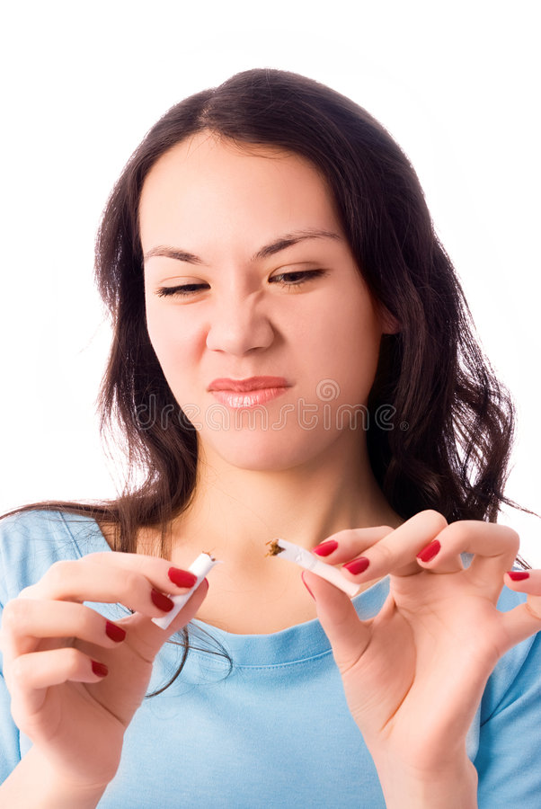 Young woman breaking a cigarette and frowning royalty free stock photos