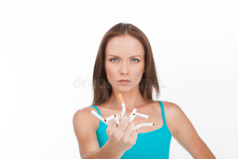 Young woman breaking up cigarette isolated on white background. Young pretty woman stops smoking and breaking cigarettes stock photography