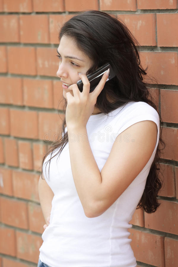 Download Young Woman At Brick Wall Talking Cellphone Stock Image - Image: 15636683
