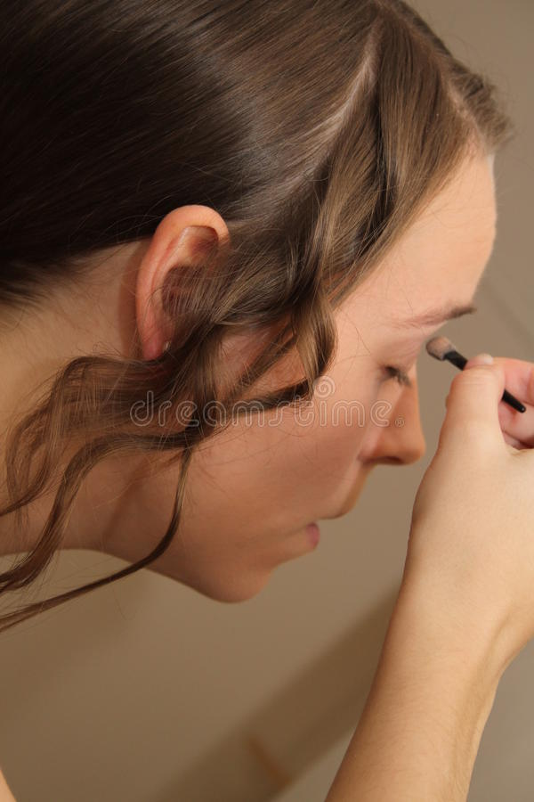 Young woman or bride applying make-up. Young attractive woman or bride applying eyeshadow to her eyelids before a wedding with a look of concentration royalty free stock images