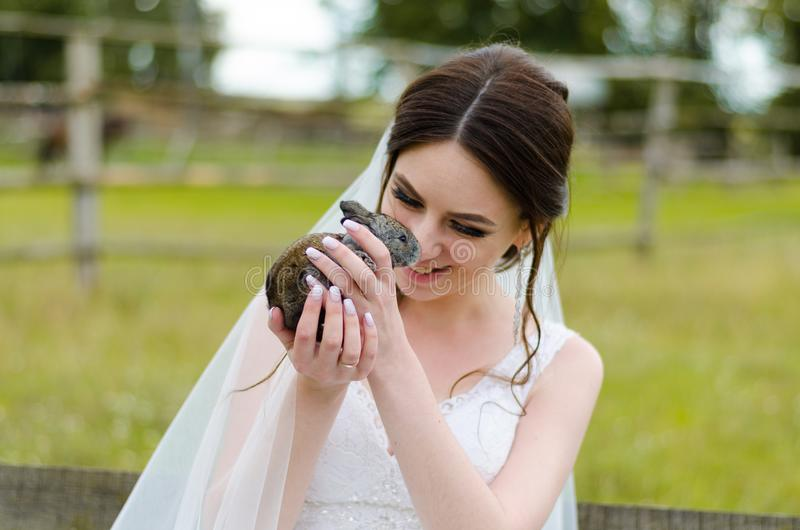 Young woman bride smiling and holding cute rabbit over park summer nature outdoor. White wedding dress, green background stock photography