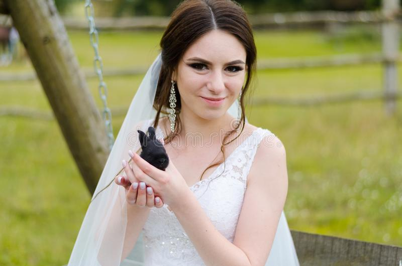 Young woman bride smiling and holding cute rabbit over park summer nature outdoor. White wedding dress, green background royalty free stock photography